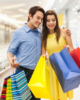 Glückliches paar, das in die einkaufstasche späht