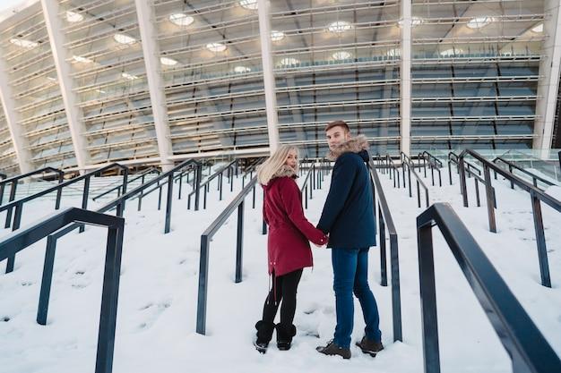 Glückliches paar, das in die straße im winter in einer stadt geht