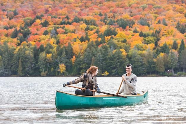 Glückliches paar, das in einem see in kanada canoeing ist