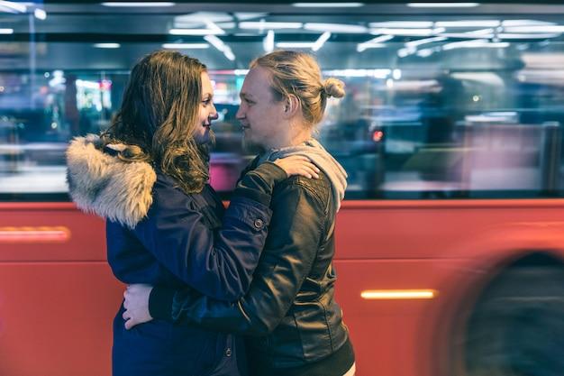 Glückliches paar, das in london mit einem roten bus umfasst