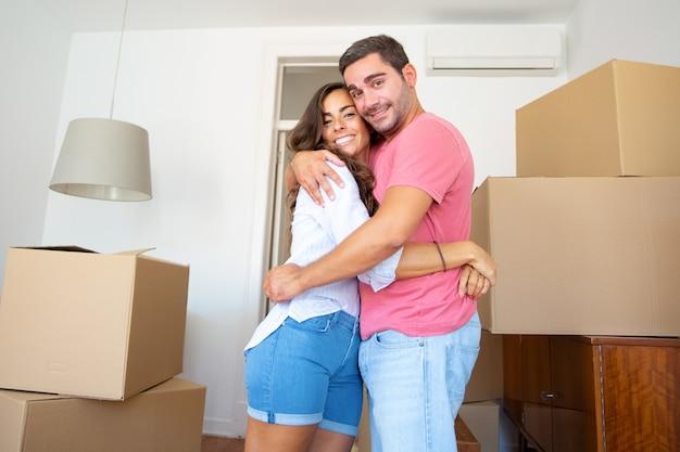 Glückliches paar, das in neue wohnung zieht, zwischen kartons steht und umarmt