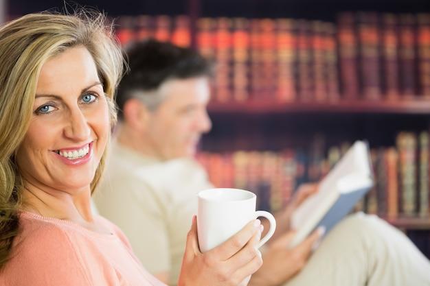 Glückliches paar, das kaffee in einem lesesaal liest und trinkt