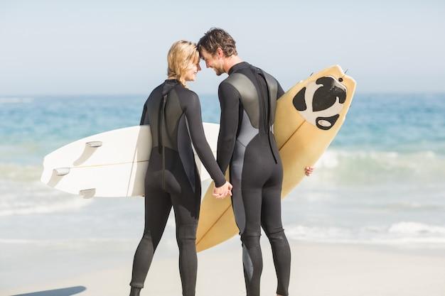 Glückliches paar, das kopf an kopf mit surfbrett steht