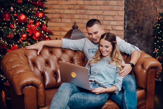 Glückliches paar, das laptop-monitor auf der weihnachtsdekoration betrachtet