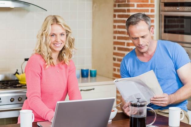 Glückliches paar, das laptop verwendet und in der küche frühstückt