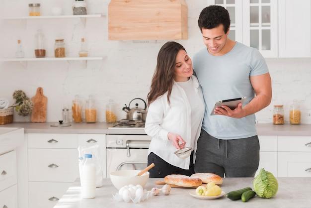 Glückliches paar, das lernt, wie man von online-rezepten kocht