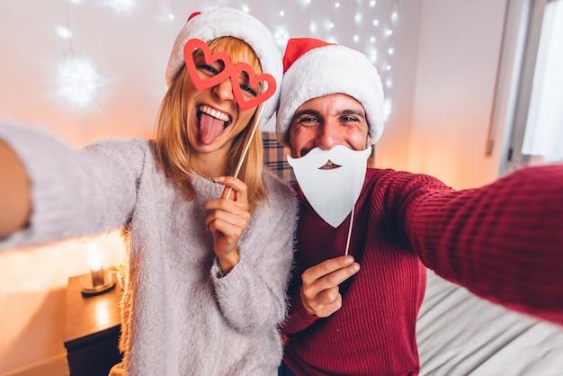 Glückliches paar, das lustiges selfie nimmt, das weihnachtszeit zu hause feiert