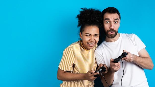 Glückliches paar, das mit gamecontrollern spielt