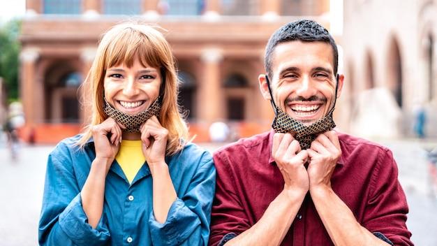 Glückliches paar, das mit geöffneter gesichtsmaske nach wiedereröffnung der sperre lächelt