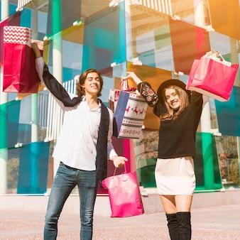 Glückliches paar, das mit hellen einkaufstaschen steht
