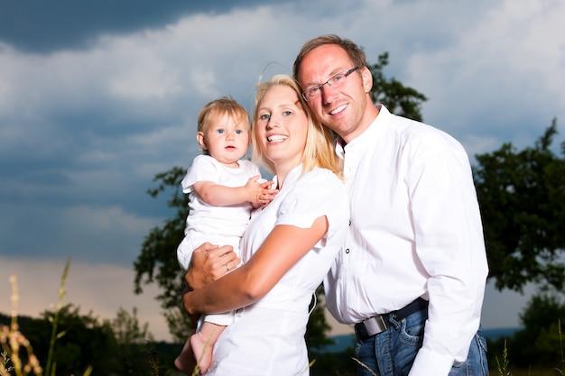 Glückliches paar, das mit ihrem baby in einem stürmischen wetter aufwirft