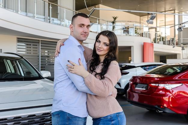 Glückliches paar, das mit neuen autos im ausstellungsraum aufwirft