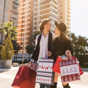 Glückliches paar, das mit weihnachtseinkaufstaschen geht