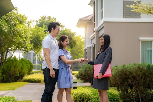 Glückliches paar, das nach ihrem neuen haus sucht und dem immobilienmakler nach einem deal die hand schüttelt.