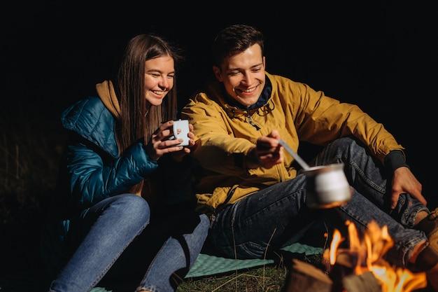 Glückliches paar, das nachts tee im wald trinkt
