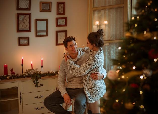 Glückliches paar, das nahe weihnachtsbaum umarmt
