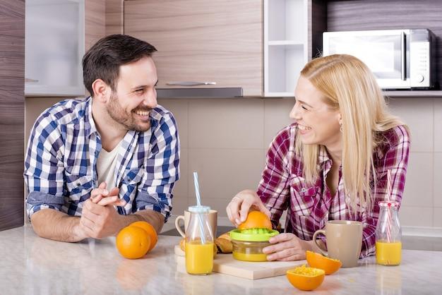 Glückliches paar, das natürlichen orangensaft in der küche macht und ihre zeit genießt