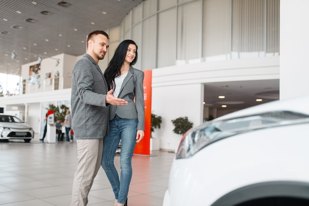 Glückliches paar, das neues auto im ausstellungsraum kauft.