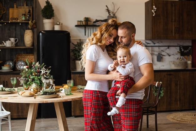Glückliches paar, das niedliches baby beim umarmen in ihrem haus hält