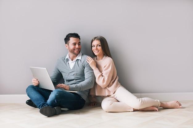 Glückliches paar, das online auf laptop einkauft, während boden zu hause sitzt.