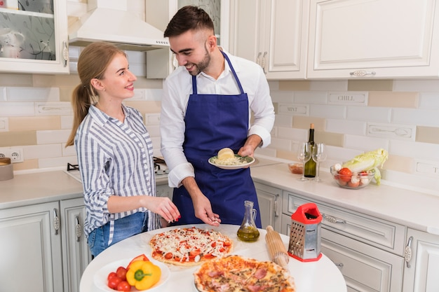 Glückliches paar, das pizza mit käse in der küche kocht