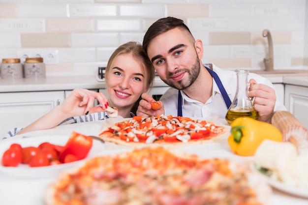 Glückliches paar, das pizza mit tomaten und pilzen in der küche kocht