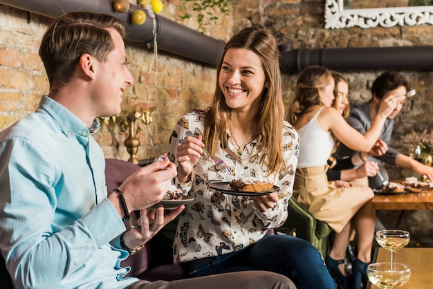 Glückliches paar, das pizzascheibe auf platte isst