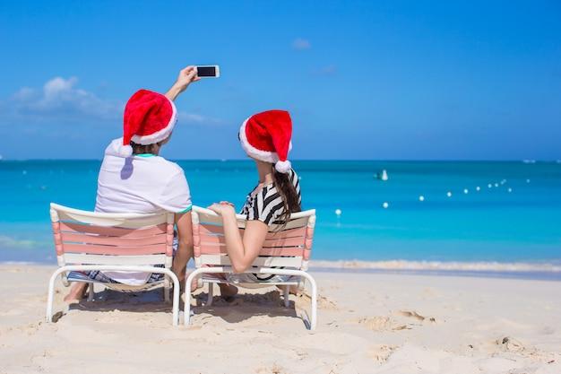 Glückliches paar, das sankt-hut am karibischen strand trägt