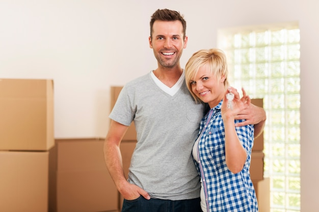 Glückliches paar, das schlüssel zum neuen zuhause hält