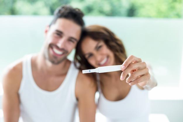 Glückliches paar, das schwangerschaftsausrüstung zeigt