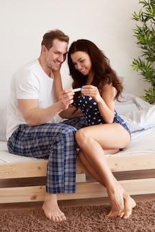 Glückliches paar, das schwangerschaftstest betrachtet