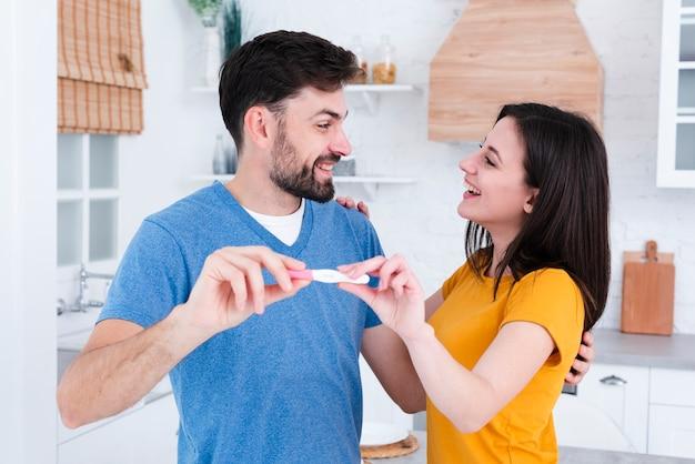Glückliches paar, das schwangerschaftstest vorführt