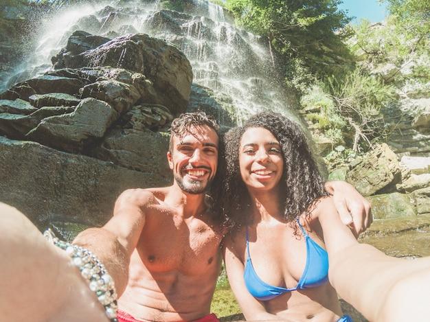 Glückliches paar, das selbstporträt mit smartphone-kamera unter tropischen wasserfällen in den sommerferien nimmt