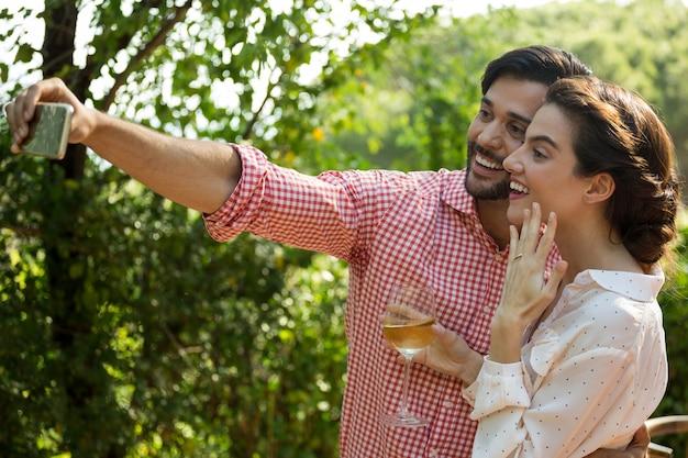 Glückliches paar, das selfie durch smartphone am park nimmt