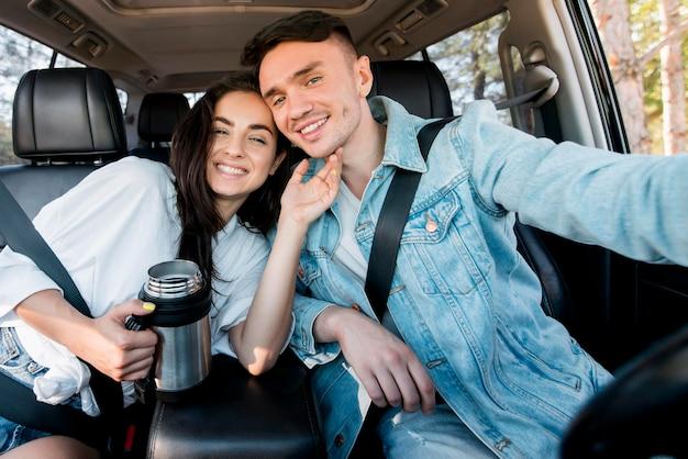 Glückliches paar, das selfie im auto nimmt