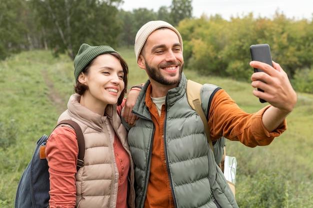 Glückliches paar, das selfie in der natur mit smartphone nimmt