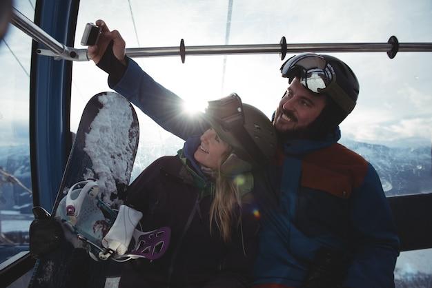 Glückliches paar, das selfie in überkopfseilbahn gegen himmel nimmt