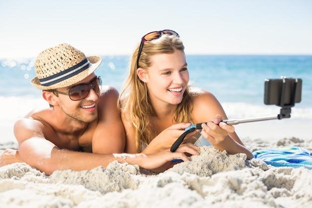 Glückliches paar, das selfie mit selfie stock nimmt