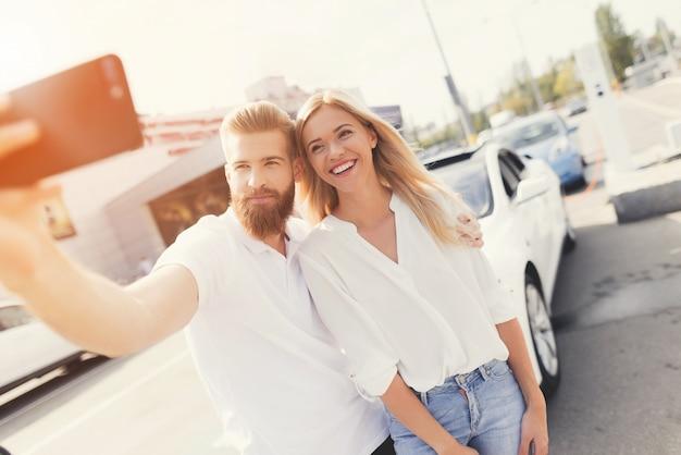 Glückliches paar, das selfie vor auto tut