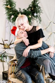 Glückliches paar, das sich im hellen raum mit weihnachtsdekorationen umarmt