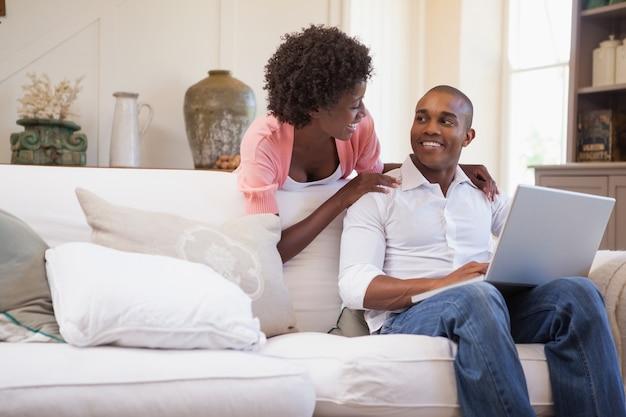 Glückliches paar, das sich zusammen auf der couch unter verwendung des laptops entspannt