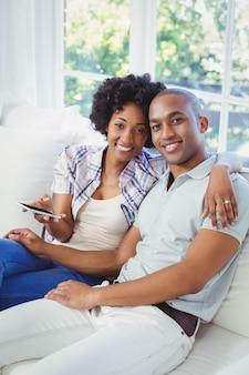 Glückliches paar, das smartphone auf dem sofa im wohnzimmer verwendet