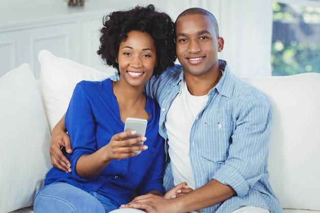 Glückliches paar, das smartphone auf dem sofa verwendet