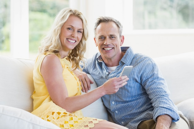 Glückliches paar, das smartphone im wohnzimmer verwendet