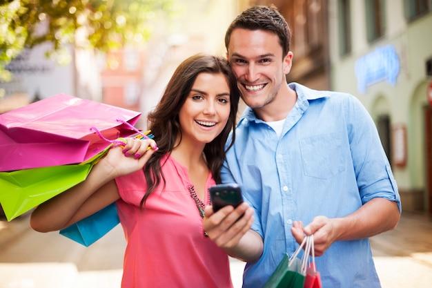 Glückliches paar, das smartphone während des einkaufs verwendet