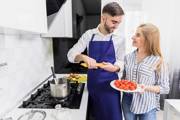 Glückliches paar, das spaghettis in topf mit gekochtem wasser einsetzt