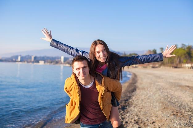 Glückliches paar, das spaß am strand an einem sonnigen falltag hat