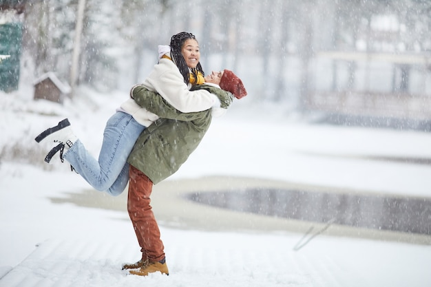Glückliches paar, das spaß draußen im winterpark hat