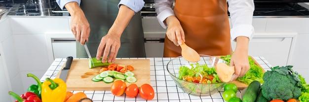 Glückliches paar, das spaß hat, in der küche zu hause stehend gemüsegemüsesalat zu stehen
