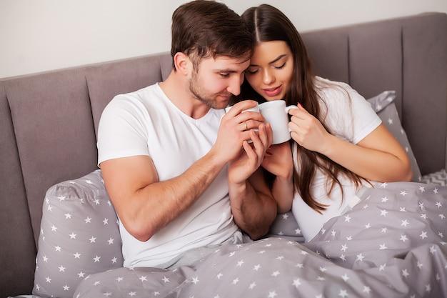 Glückliches paar, das spaß im bett hat. intimes sinnliches junges paar im schlafzimmer, das sich gegenseitig genießt